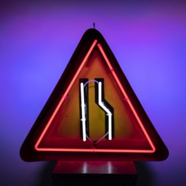 neon road sign - the road narrows